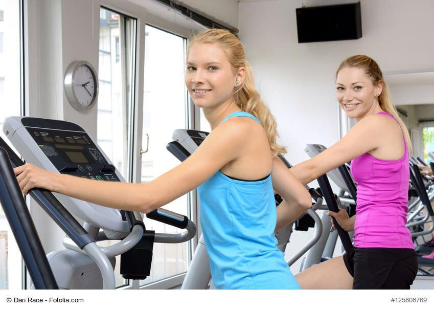 Frauen beim Aufwrmen auf Crosstrainer in Fitnessclub
