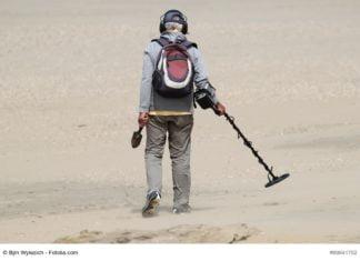 해변에서 금속 탐지기를 가진 남자