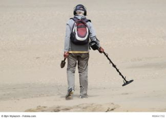 Man med metalldetektor på stranden