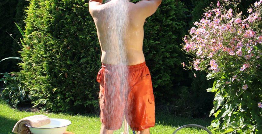 Mann unter der Gartendusche